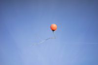 Low angle view of buoy in mid-air against blue sky