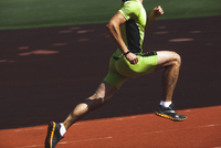 Low section of sporty young man running on race track