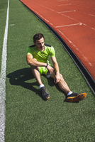 Full length of male athlete with water bottle relaxing on sports field
