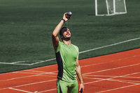 Young male athlete pouring water on face in stadium