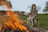 Girl and dog sitting by bonfire on field