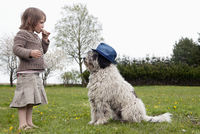 Full length side view of girl eating in front of dog on field