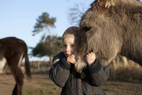 Cute girl embracing donkey on field