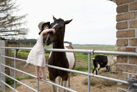 Girl embracing horse while standing on railing at farm