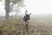 Girl riding donkey on field during foggy weather