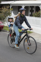 Full length of mother cycling while son sitting on back seat