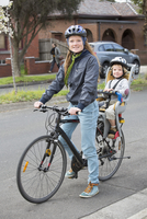 Portrait of mother cycling while son sitting on back seat