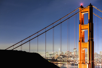 Golden Gate Bridge with illuminated cityscape in background