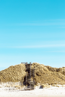 Stairway over sand dune at beach against sky