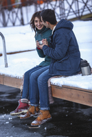 Full length of happy young couple having coffee on pier