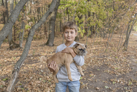 Portrait of cute boy carrying dog in forest