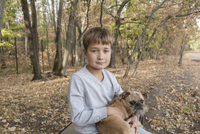 Portrait of cute boy sitting with dog in forest during autumn