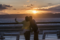 Rear view of couple taking selfie at railing by sea during sunset