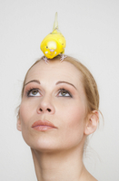 Beautiful woman looking at yellow budgerigar perching on head against white background