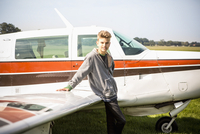 Portrait of teenage boy leaning on private airplane