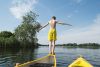 Rear view of boy jumping from canoe in lake