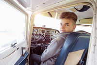 Rear view portrait of teenage boy sitting in private airplane