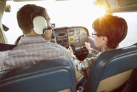 Rear view of father and son in cockpit of private airplane