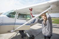 Portrait of happy teenage boy standing outside private airplane