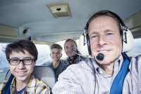 Portrait of men and teenage boys in private airplane