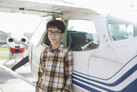 Portrait of confident teenage boy standing outside private airplane