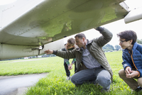 Father explaining airplane parts to sons on field
