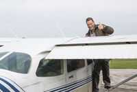 Portrait of happy man gesturing thumbs up while standing on private airplane against sky