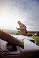 Side view portrait of man gesturing thumbs up by private airplane against sky