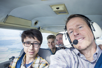 Portrait of men and teenage boys sitting in private airplane