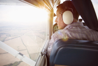 Rear view of man looking through private airplane window