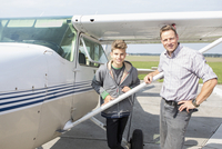 Portrait of happy father and son standing outside private airplane