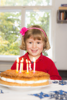 Happy girl looking at birthday cake on table
