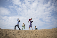 Low angle view of family enjoying on sand dune against cloudy sky