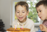 Boy looking at brother blowing birthday candles