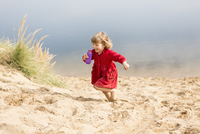 Cheerful girl holding water bottle while running on sand dune