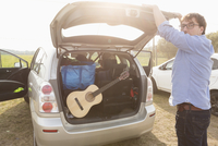 Side view of man closing car trunk