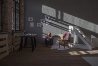 Woman sitting on floor in art studio