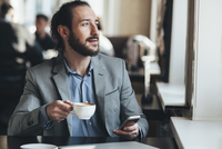Mid adult businessman holding coffee cup and mobile phone in cafe