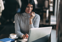 Young businesswoman using laptop at table in cafe