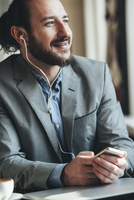 Happy businessman listening music through mobile phone in cafe