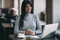 Portrait of happy young businesswoman with laptop at cafe table