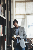 Mid adult businessman reading book in cafe