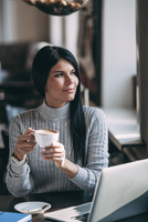 Young businesswoman having coffee at table in coffee shop