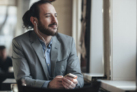 Thoughtful businessman listening music through mobile phone in cafe