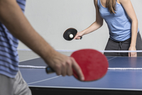 Midsection of man and woman playing table tennis