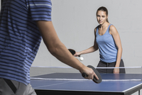 Confident young woman playing table tennis with man