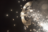 Illuminated euro symbol with fireworks at night