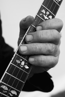Cropped image of hand playing guitar against gray background