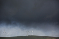 Stormy clouds over wind turbines on agricultural field