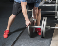 Low section of man adding weights on barbell
